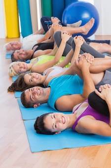 La gente che allunga le gambe in classe di yoga