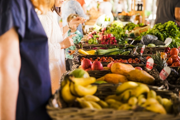 La gente che compra verdura sulla stalla al mercato