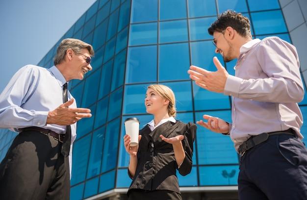 La gente che discute di progetto stando in piedi davanti all'ufficio.