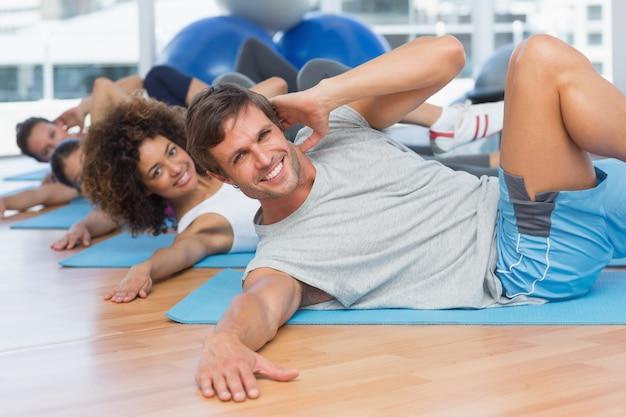 La gente che fa gli esercizi del pilate nello studio di forma fisica