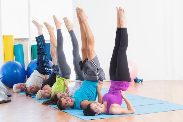 La gente che fa gli esercizi di pilates in palestra