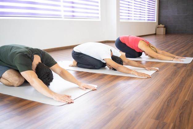 La gente che fa posa del bambino alla classe di yoga
