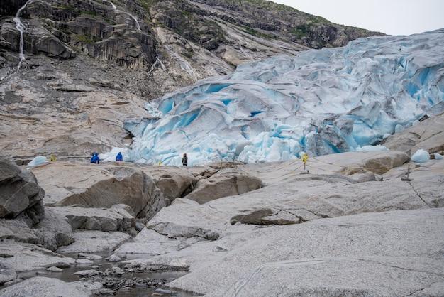 La gente che fa un'escursione al ghiacciaio blu nelle montagne