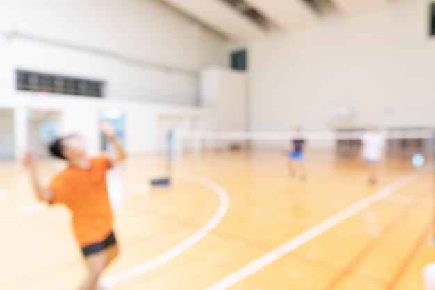 La gente che gioca a badminton in doppia squadra gioca in palestra