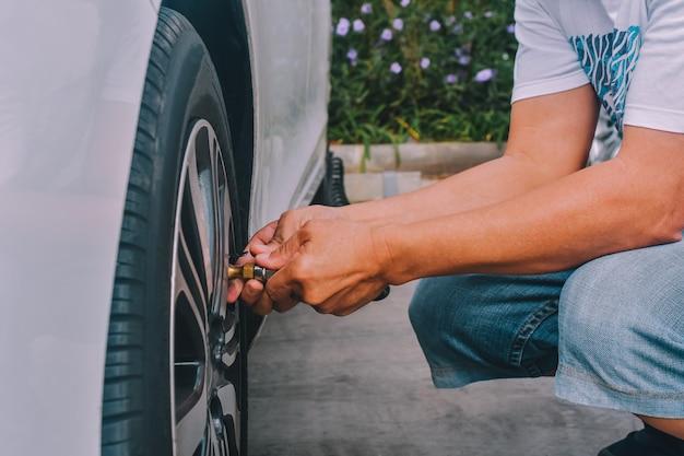 La gente che gonfia le gomme dell'auto parcheggiata