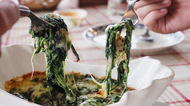La gente che mangia il formaggio di spinaci cuoce la ricetta