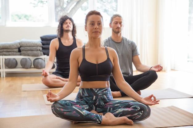 La gente che medita e che si tiene per mano nel gesto di mudra in classe