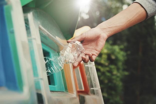 La gente che mette la bottiglia di plastica per riciclare il recipiente al parco
