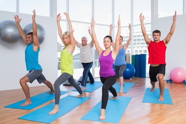 La gente che si esercita con le mani sollevate al club di forma fisica