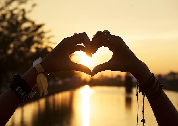 La gente che si fa le mani nel tramonto della siluetta di forma del cuore