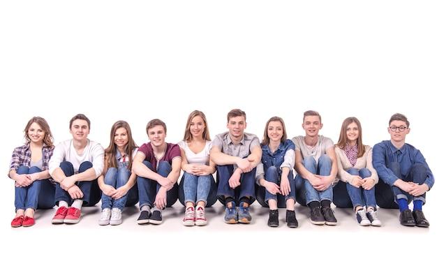 La gente che si siede insieme sul pavimento sul bianco