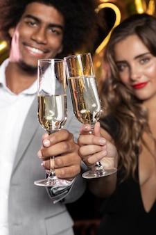 La gente che sorride e che tiene i vetri del primo piano del champagne