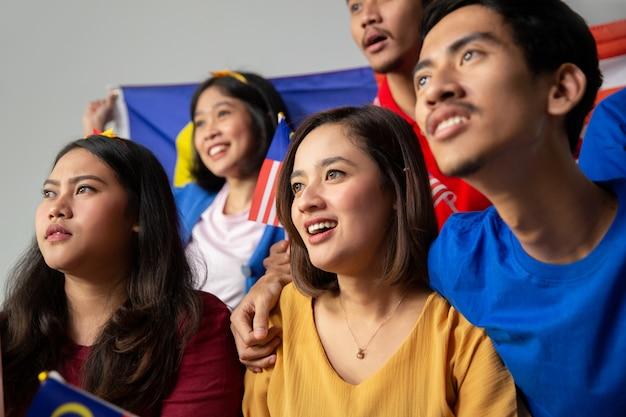 La gente che tiene la bandiera della malesia che celebra la super league della malesia