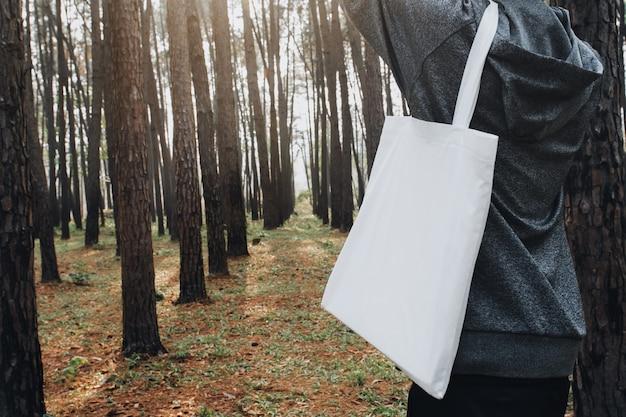 La gente che tiene la borsa del cotone per lo spazio in bianco del modello nel fondo della natura