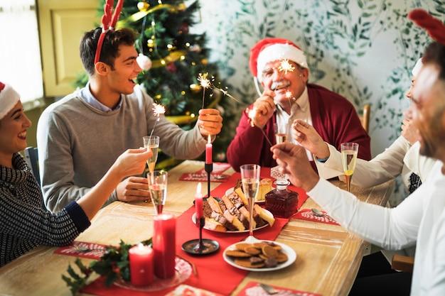 La gente con i fuochi del bengala al tavolo festivo