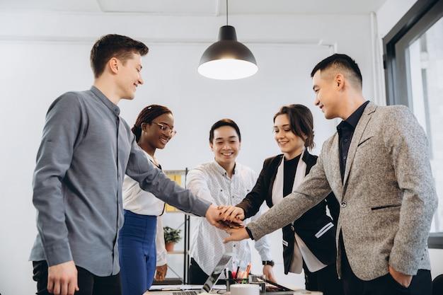 La gente del gruppo di affari euforico multirazziale dà il cinque al tavolo dell'ufficio, il gruppo di lavoro vario eccitato felice impegnato nel team building celebra il successo aziendale vince il concetto di lavoro di squadra di potere di associazione