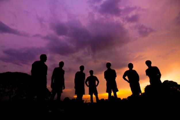 La gente della siluetta equipaggia la felicità di successo della celebrazione su un tramonto di pietra del cielo di sera