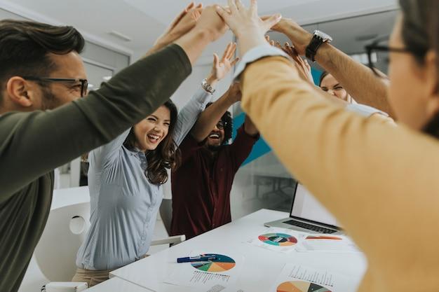 La gente della squadra che impila le mani insieme sopra la tavola si è impegnata nel teambuilding