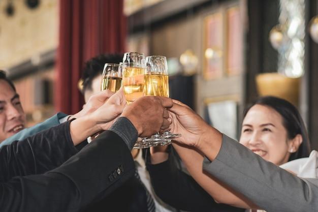 La gente di affari asiatica che beve celebra il successo aziendale felice