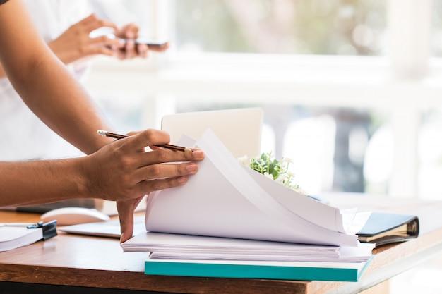 La gente di affari asiatica lavora e studia insieme al taccuino del documento