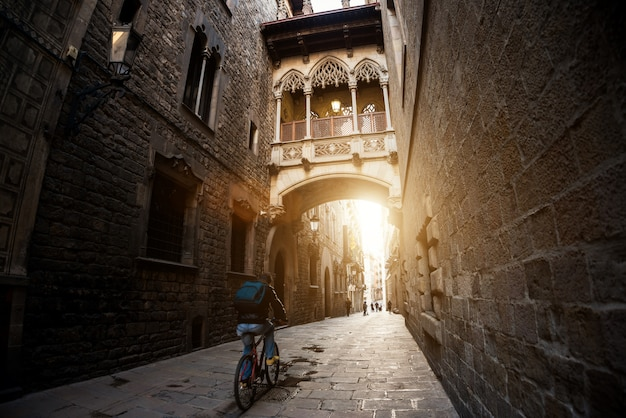 La gente di barcellona che biking va in bicicletta nel quartiere gotico di barri a barcellona, catalogna, spagna.