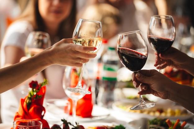 La gente festeggia e alza bicchieri di vino per brindare