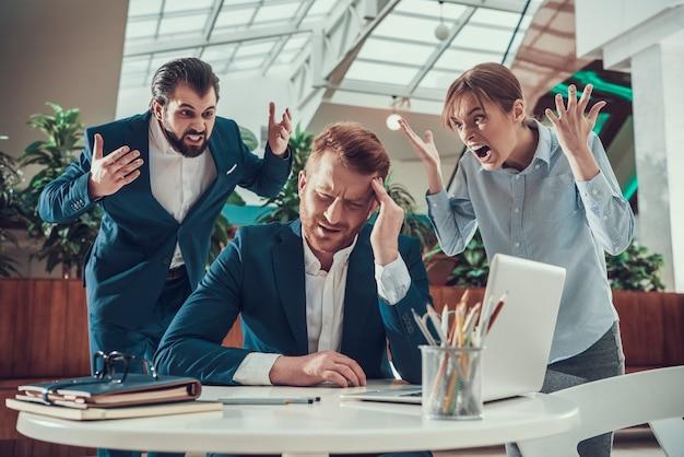 La gente grida al lavoratore in difficoltà in tuta in ufficio.