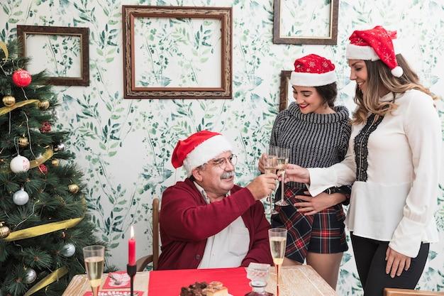 La gente in cappelli di babbo natale fracasso bicchieri di champagne