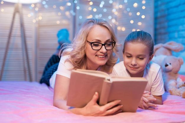 La gente legge insieme il libro sul letto.