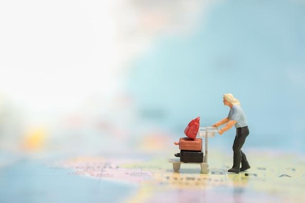 La gente miniatura cammina con il carrello / carrello dell'aeroporto con i bagagli sulla mappa di mondo.
