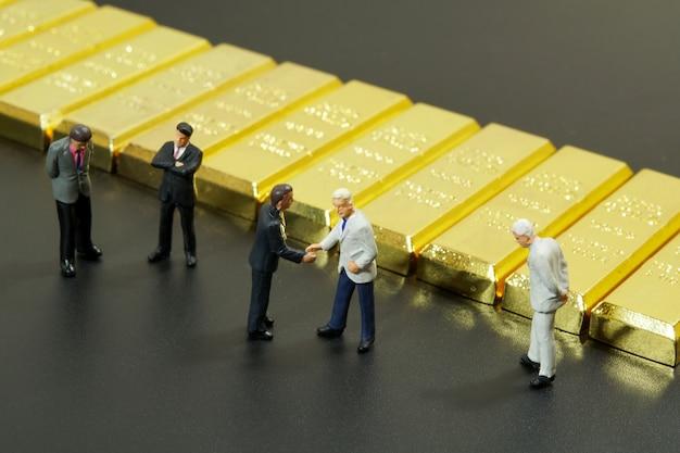 La gente miniatura che stringe la mano con la pila di barra di oro su fondo nero