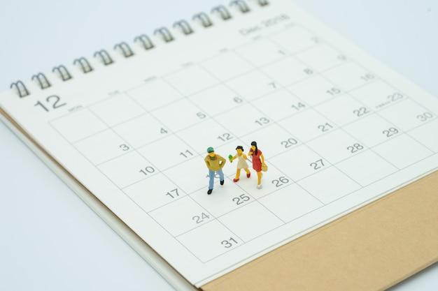La gente miniatura della famiglia che si leva in piedi sul calendario celebra il natale