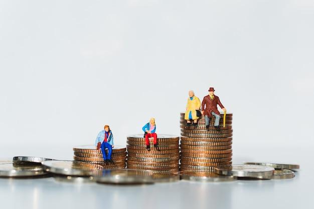 La gente miniatura della famiglia che si siede sulle monete della pila facendo uso come pensione di lavoro e concetto di assicurazione