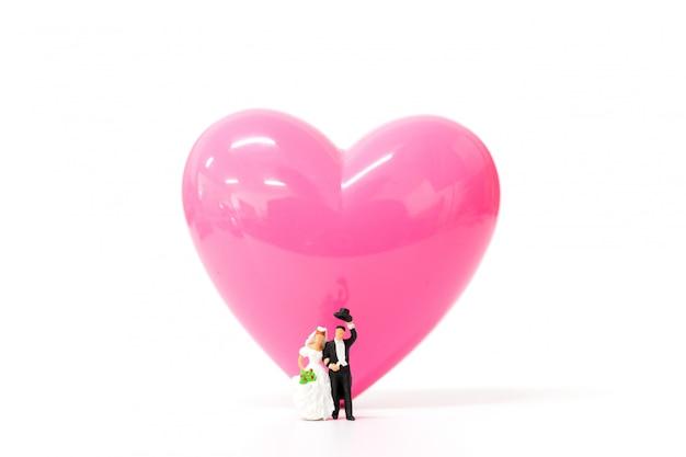 La gente miniatura si accoppia con cuore rosa su fondo bianco