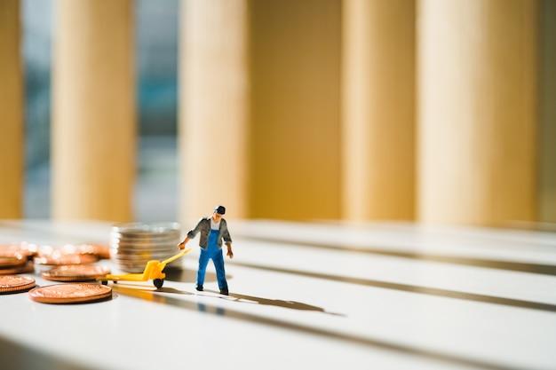 La gente miniatura, uomo che tira le monete della pila, usando per il concetto logistico, di affari e di finanza
