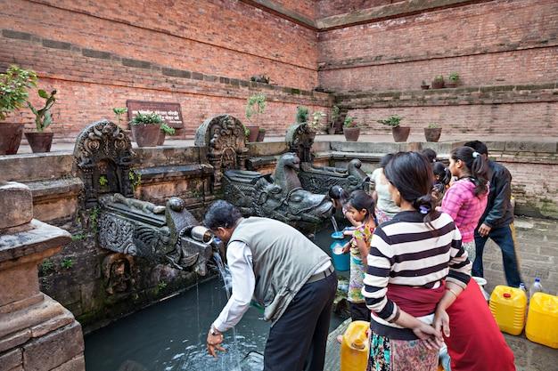 La gente nepalese raccoglie acqua