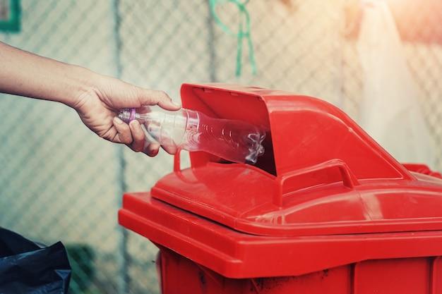 La gente passa la plastica di plastica della bottiglia di immondizia della tenuta che mette nel recipiente di riciclaggio per pulire