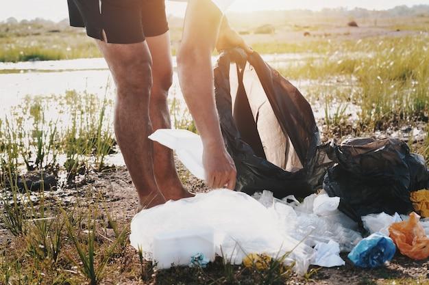 La gente passa raccogliendo la plastica dell'immondizia per la pulizia al parco del fiume