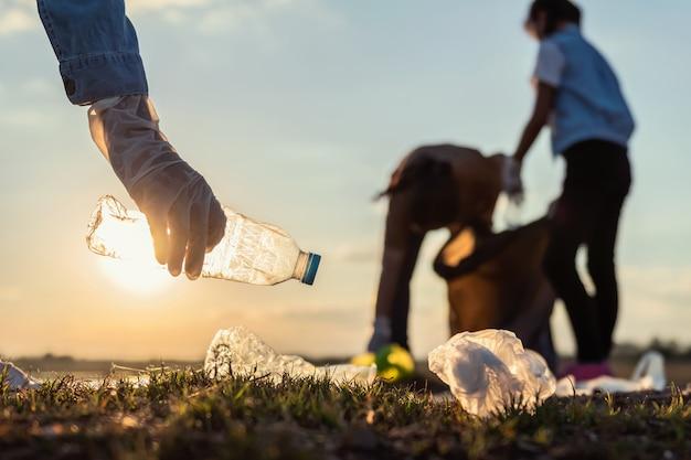 La gente si offre volontaria tenendo la bottiglia di plastica dell'immondizia nella borsa nera al fiume del parco nel tramonto