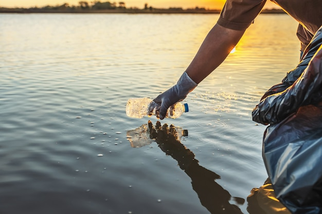 La gente si offre volontaria tenendo la bottiglia di plastica dell'immondizia nella borsa nera sul fiume nel tramonto