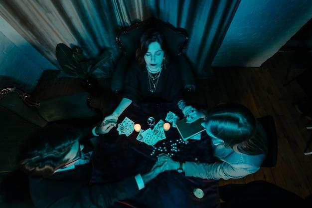 La gente tiene le mani della notte al tavolo con le candele