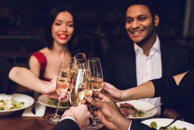 La gente tintinnano di bicchieri di champagne in un ristorante.
