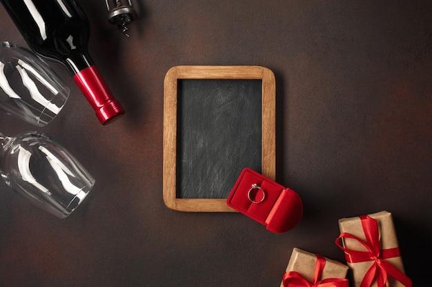 La giornata di alentine con cuori, vino, cavatappi, bicchieri, regali, una scatola a forma di cuore e una lavagna