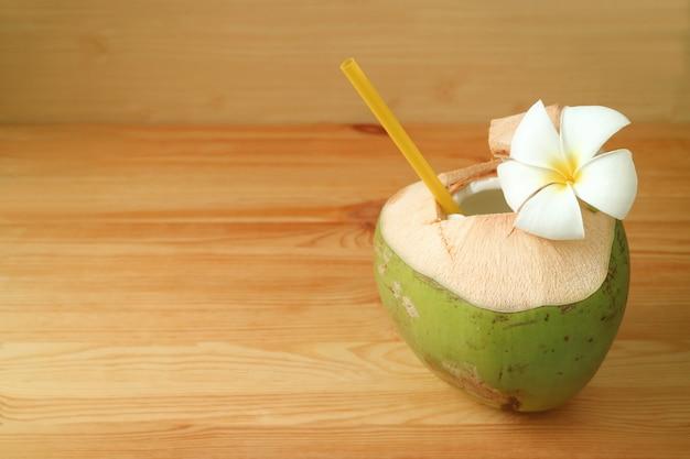 La giovane acqua di cocco fresca nelle coperture della noce di cocco con la plumeria fiorisce sulla tavola di legno