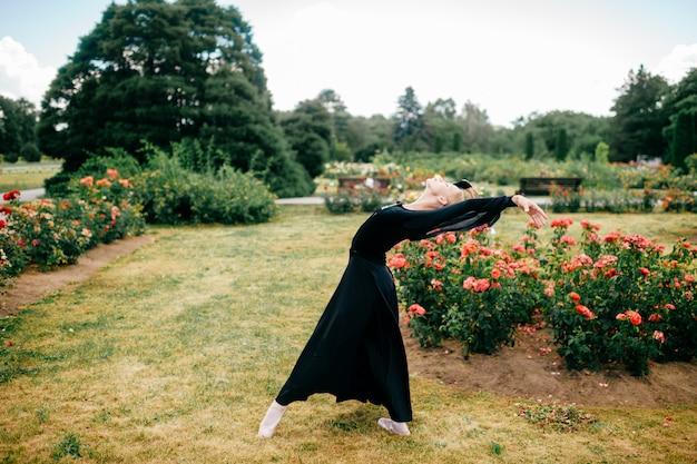 La giovane ballerina in vestito nero che mostra il balletto posa nel parco