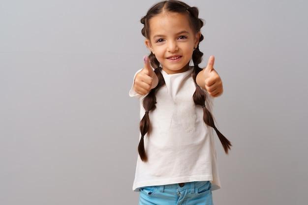 La giovane bambina felice che mostra bene firma sopra il fondo grigio