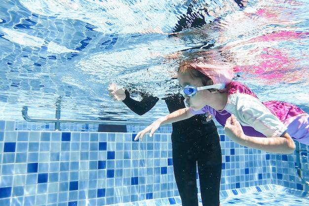 La giovane bambina sveglia subacquea sta nuotando nella piscina con il suo insegnante di nuoto.