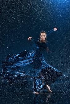 La giovane bella ballerina moderna che balla sotto le gocce d'acqua