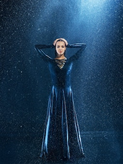 La giovane bella ballerina moderna danza sotto le gocce d'acqua