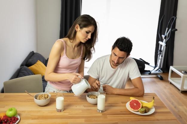 La giovane bella coppia mangia il cereale da prima colazione con le bacche e il latte.